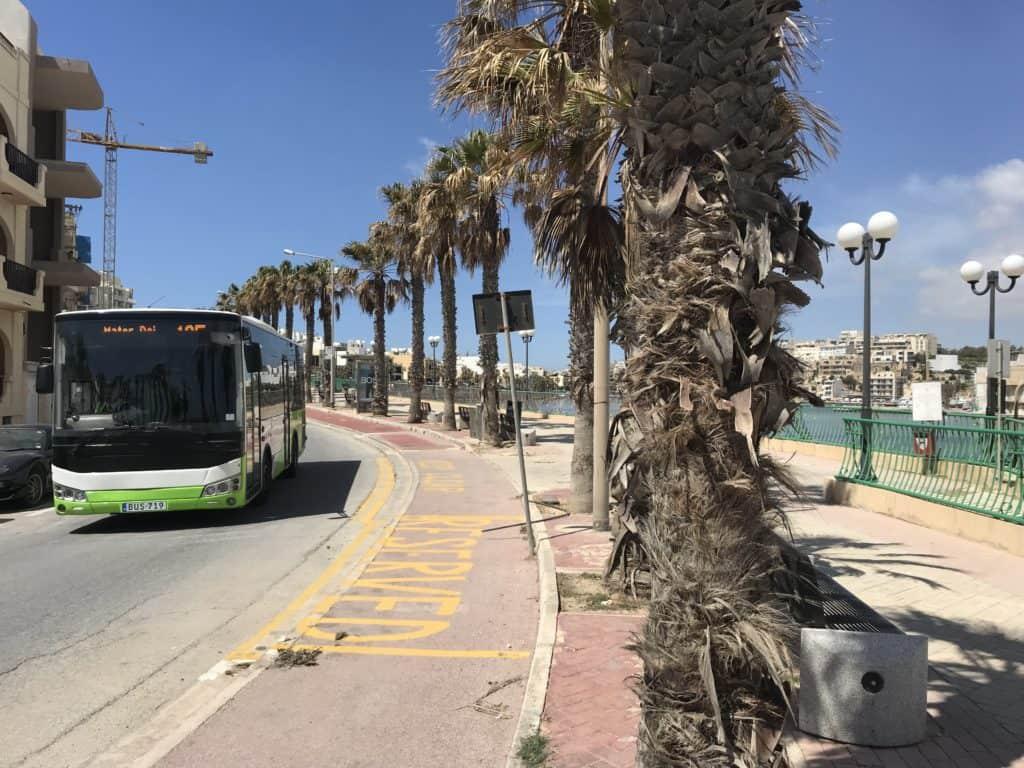 A public bus driving down the road in Malta.