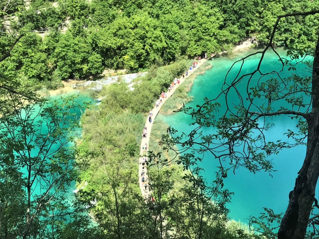 Boardwalk with blue water on either side at Plitvice Lakes National Park.