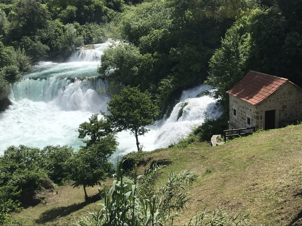 A view of the Krka waterfalls with a stone house beside them.