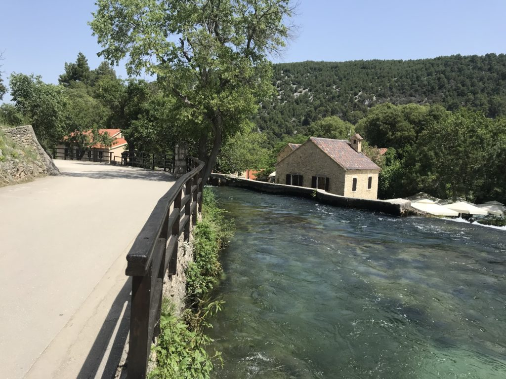 A paved road that runs beside the river at Krka.