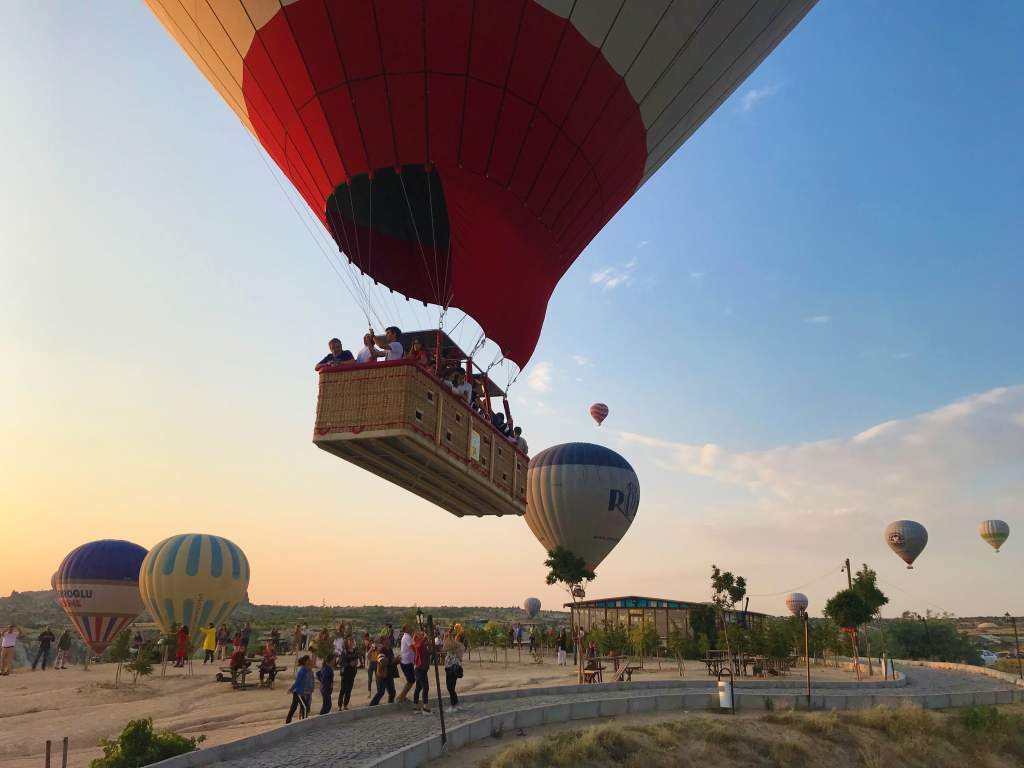 A hot air balloon nearly touching people standing in the viewing area.
