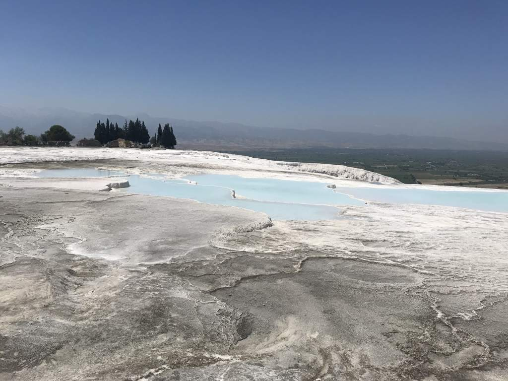 A view of Pamukkale with both blue water and grey, dry tavertines.