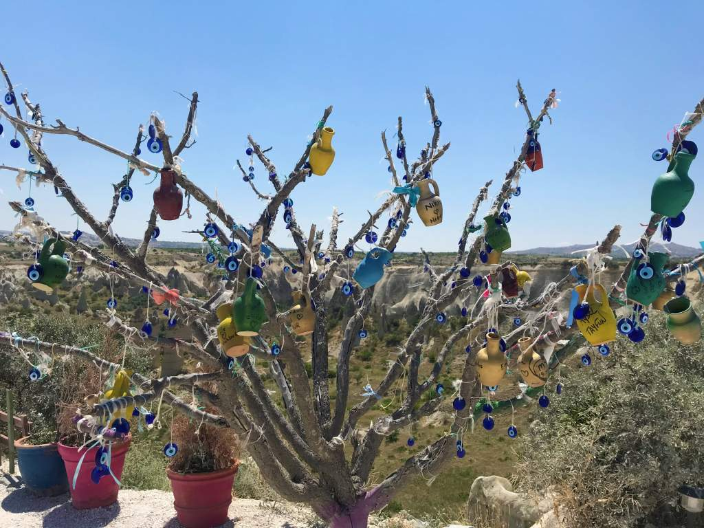 Colorful pots and trinkets hanging from a tree.