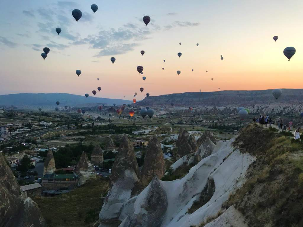 Hot air balloons flying over an accessible viewpoint in Cappadocia.