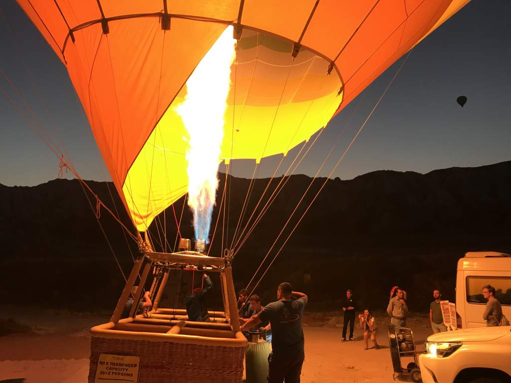 A hot air balloon with fire ignited waiting for people to get in the basket.