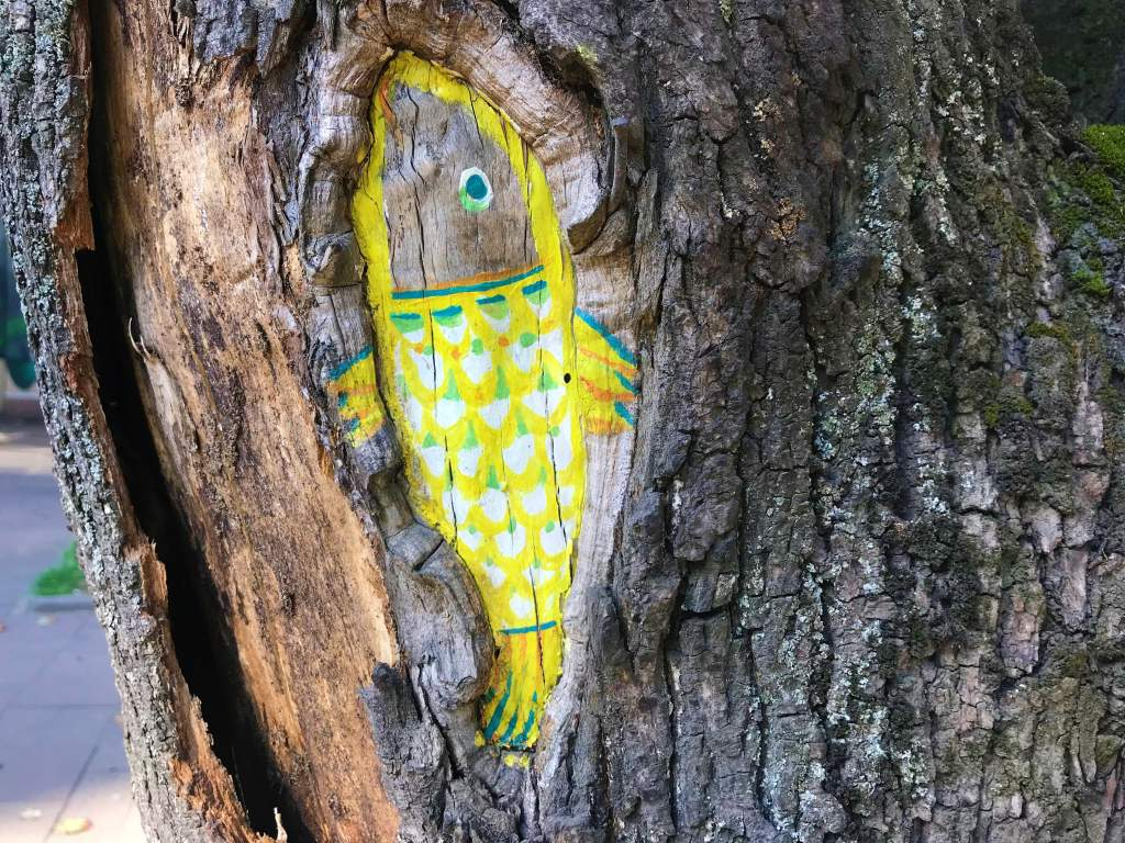 A yellow fish painted on a tree in Lviv.