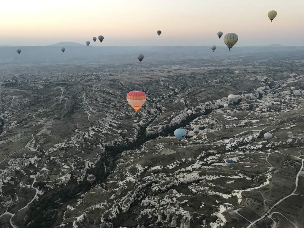 Hot air balloons flying over a scenic Cappadocia countryside landscape.