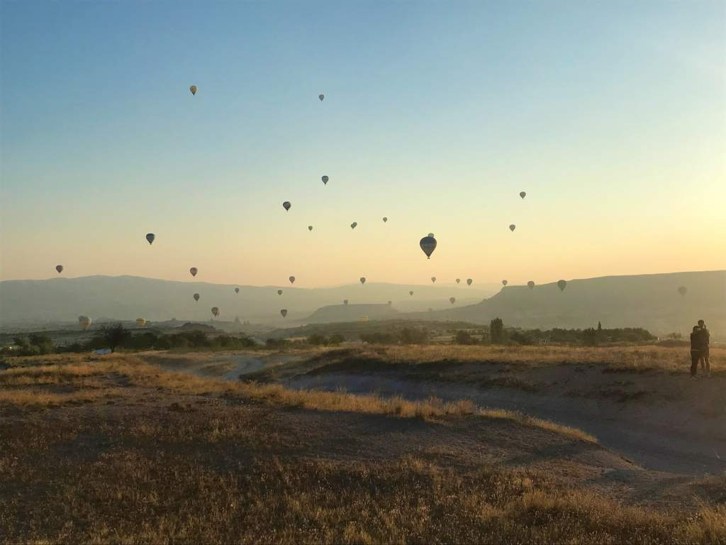 A view of hot air balloons still floating after my balloon landed in a beautiful countryside area.