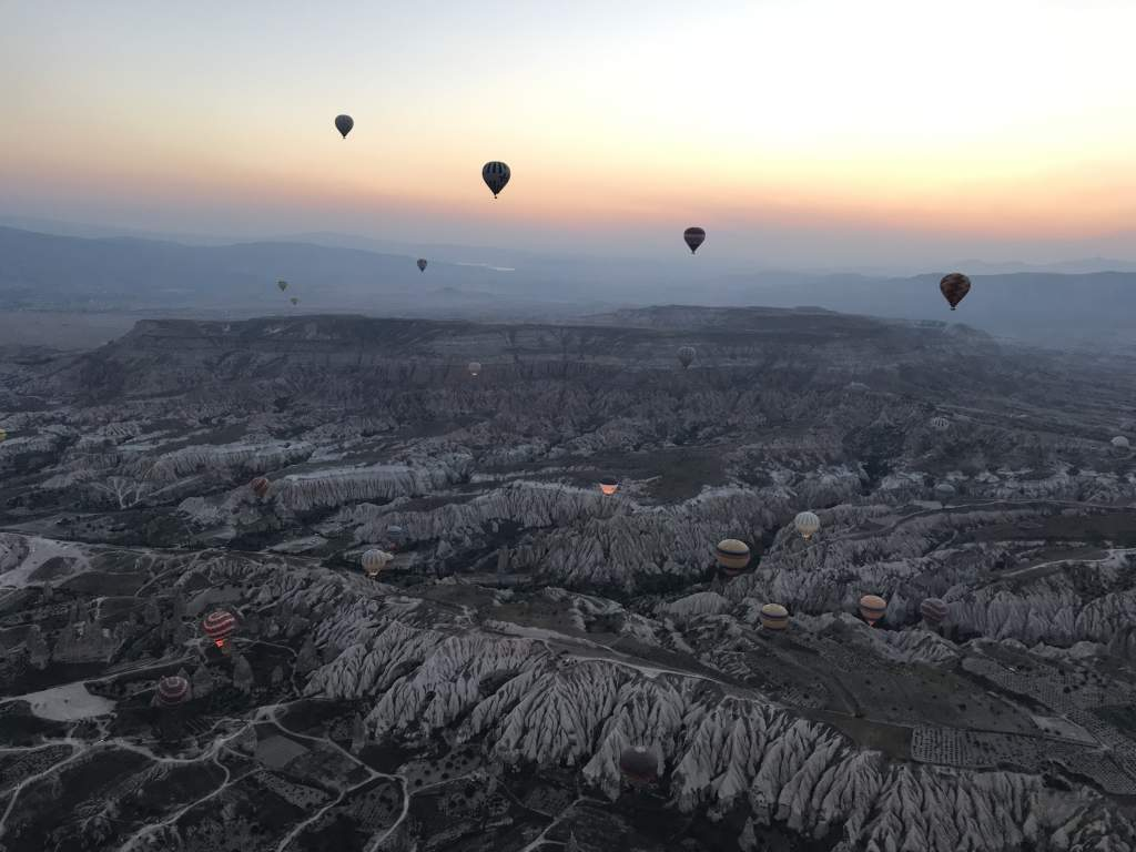 Hot air balloons flying in Cappadocia just before sunrise.