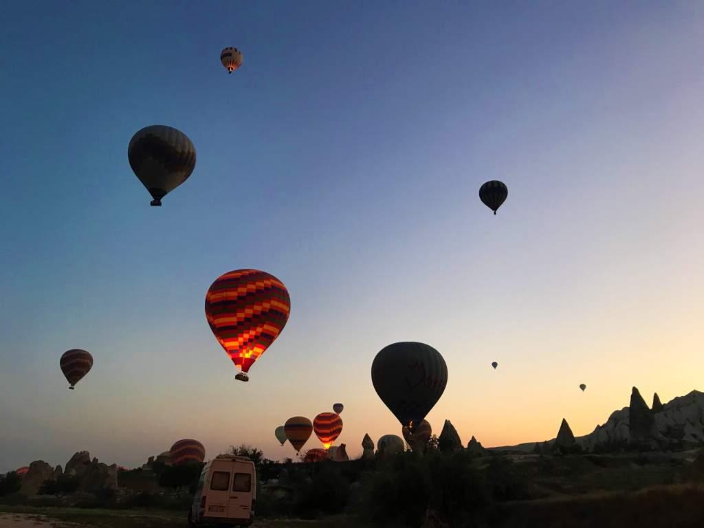 Hot air balloons taking off before sunrise in Cappadocia.