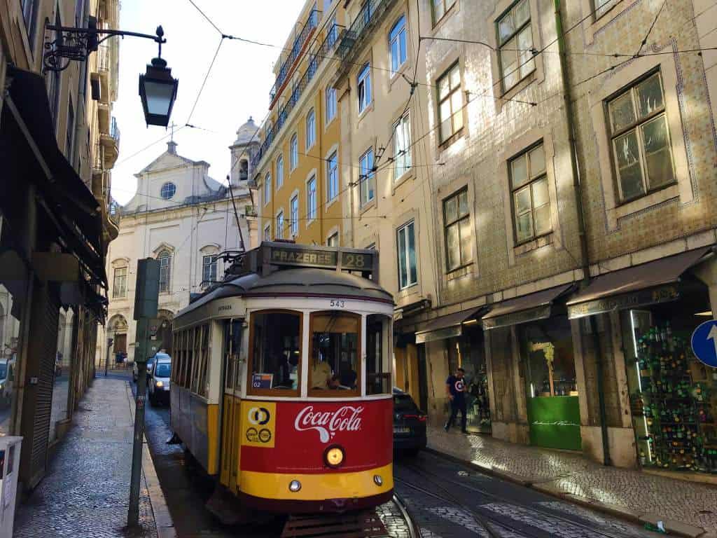 An old tram running through a narrow street.