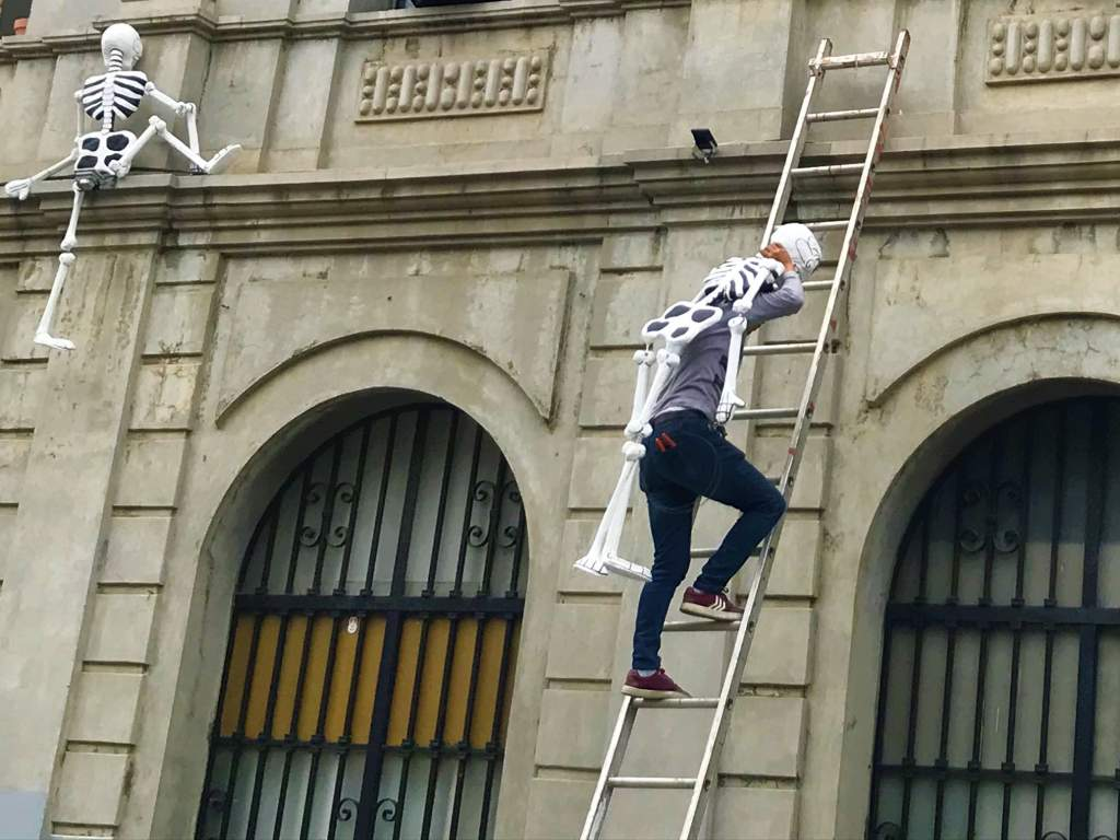 A man going up the ladder with a skeleton to decorate for Day of the Dead.