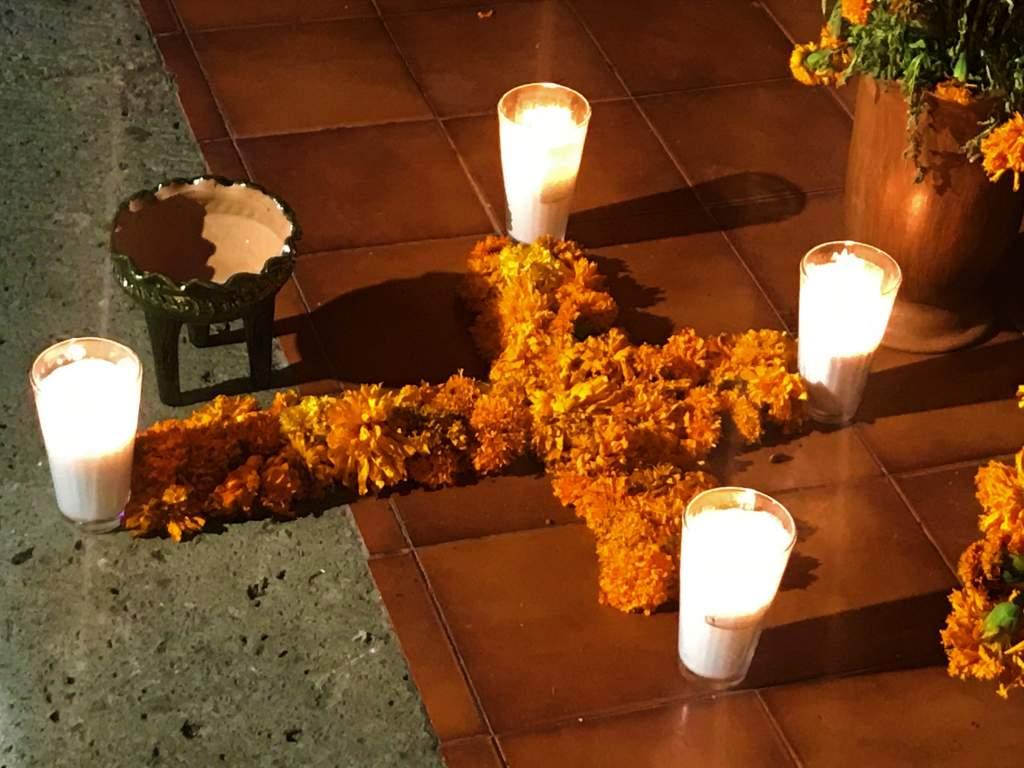 A marigold cross let with candles during Day of the Dead.