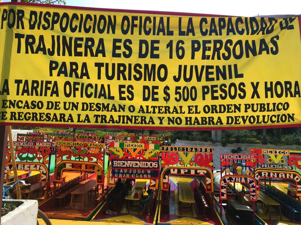 A sign indicating the price per boat is 500 pesos per boat with a maximum of 16 passengers per boat.
