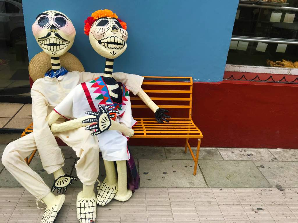 A Mexican skeleton couple on a bench in Oaxaca for Day of the Dead.