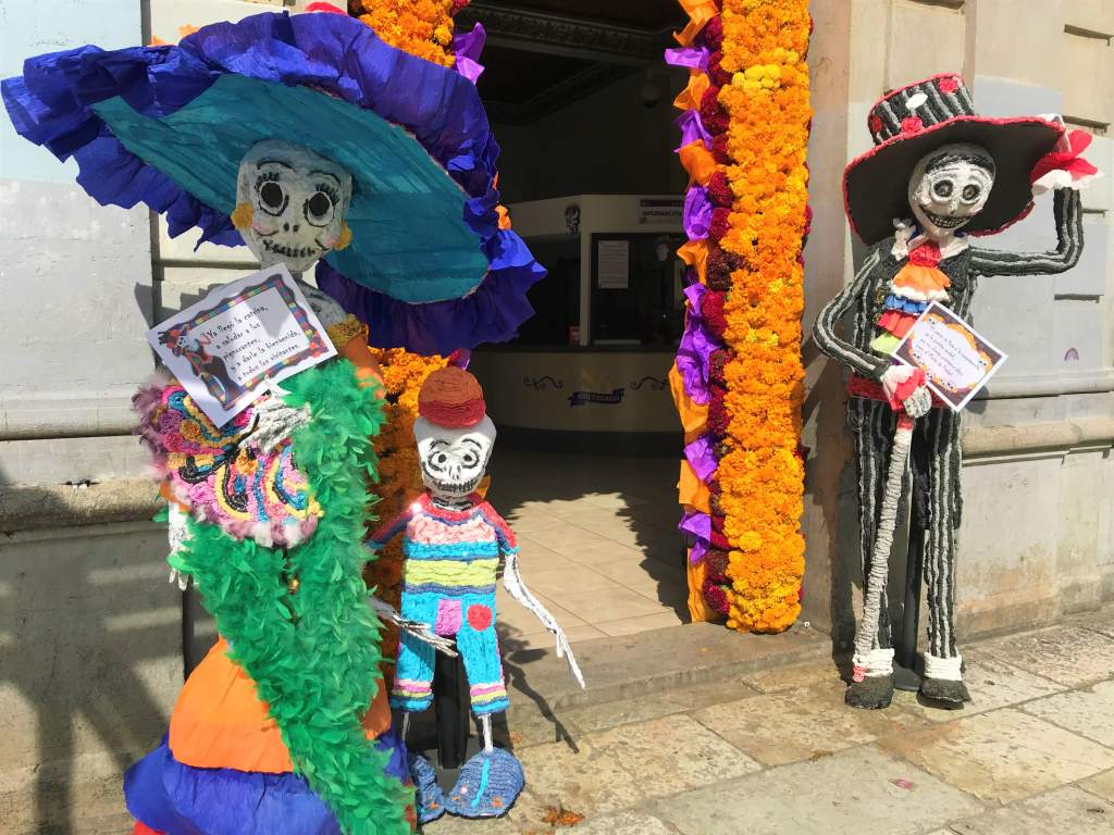 A skeleton family greeting customers outside of a business in Oaxaca.