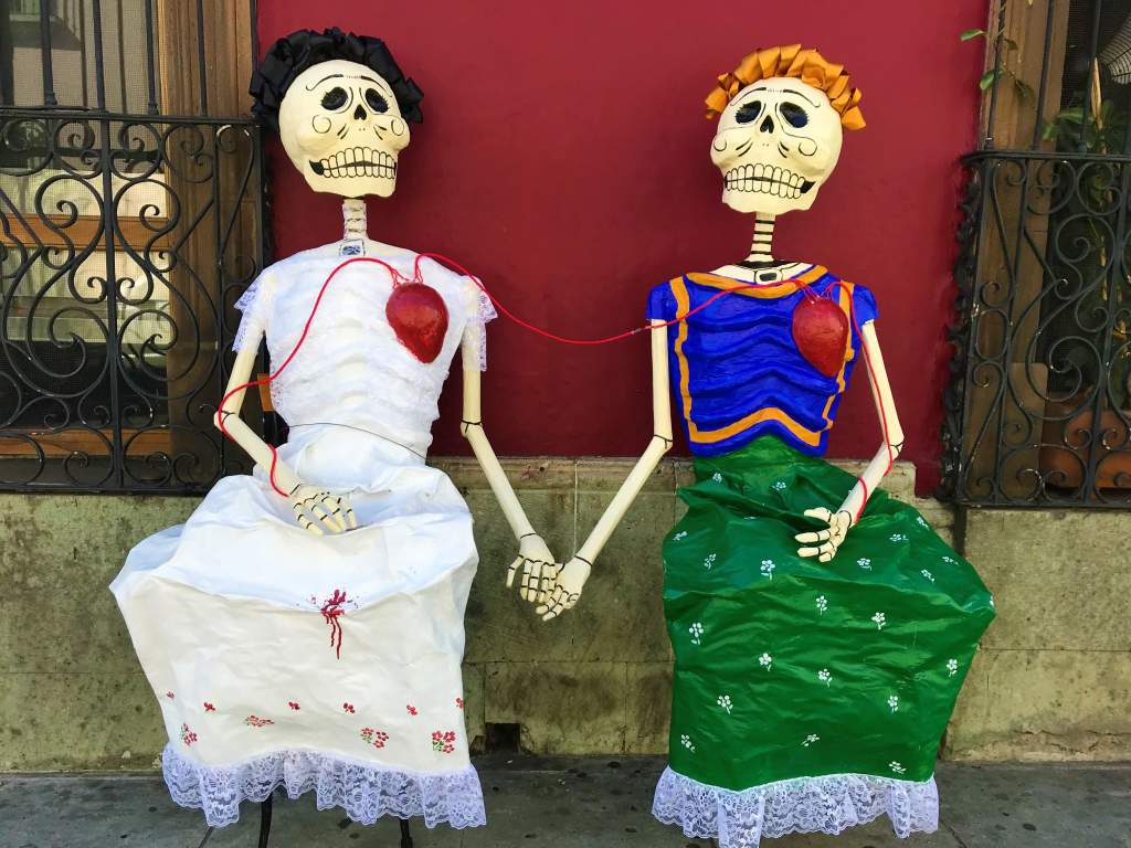 Two skeleton grandmas with hearts in Oaxaca for Day of the Dead.