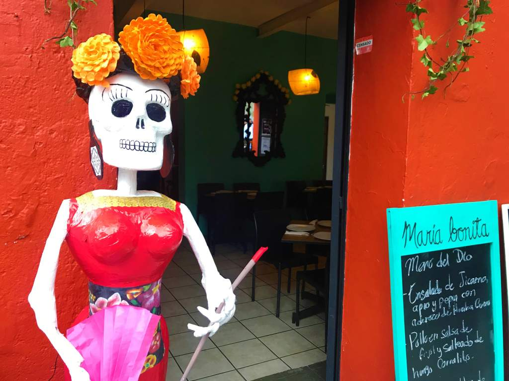 A voluptuous skeleton at the entrance to a restaurant.