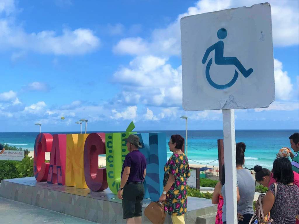 """A wheelchair sign by one of the famous, colorful """"Cancun"""" signs."""