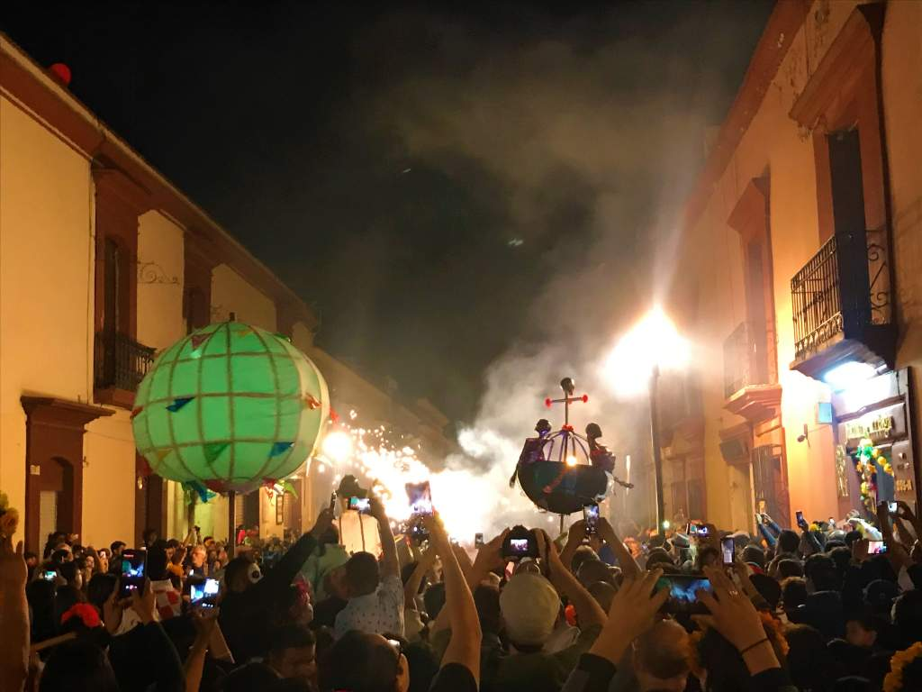 A nighttime Day of the Dead parade in the streets of Oaxaca.
