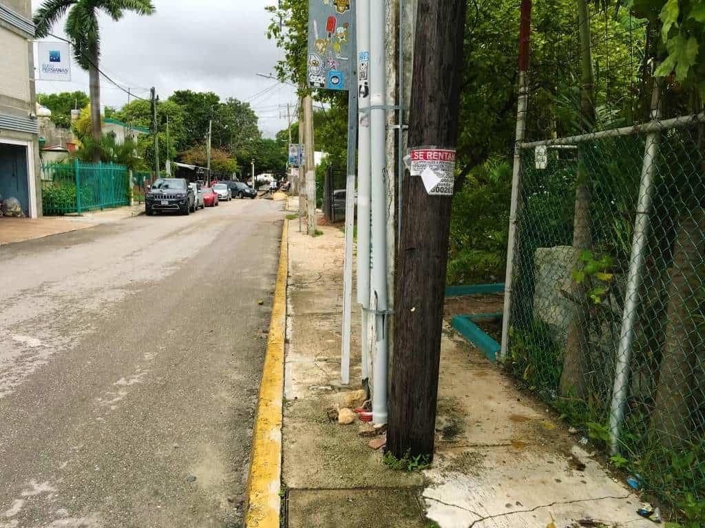 A narrow, crumbling sidewalk in downtown Cancun.