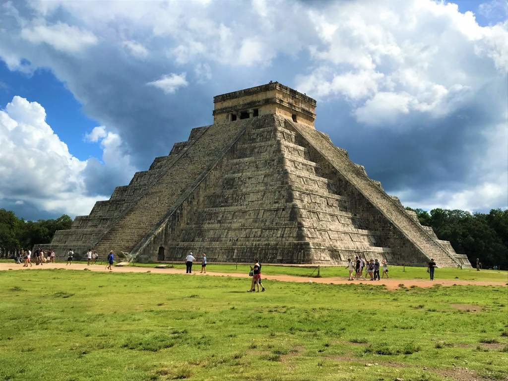 A panoramic view of the El Castillo pyramid with clouds in the backdrop.