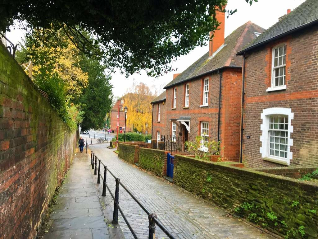 A side street in Guildford with moss covered brick buildings.