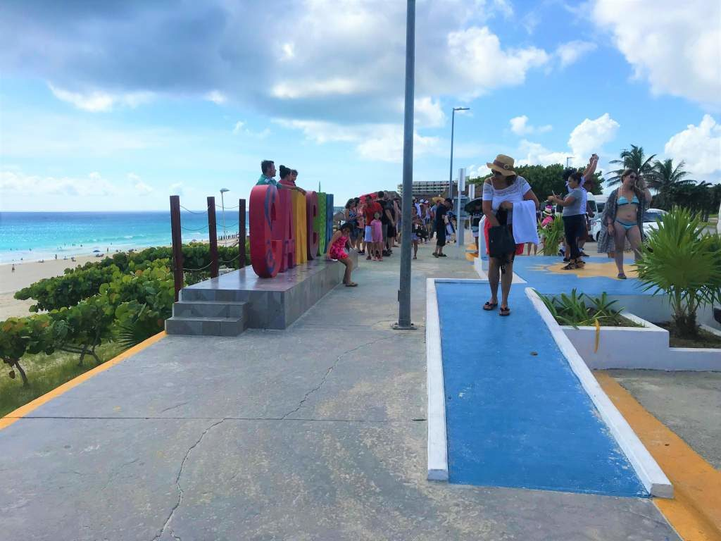 """A wheelchair accessible ramp leading to a viewing area of the """"Cancun"""" sign."""