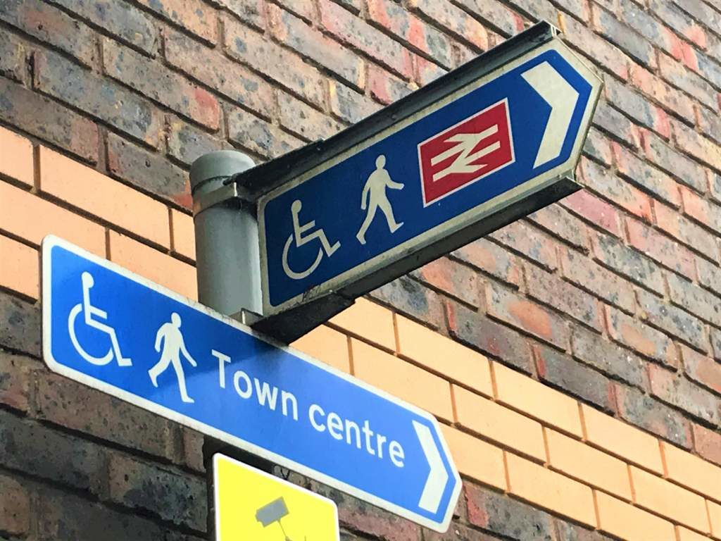 A wheelchair accessible sign pointing to downtown Guildford and the Guildford Train Station.