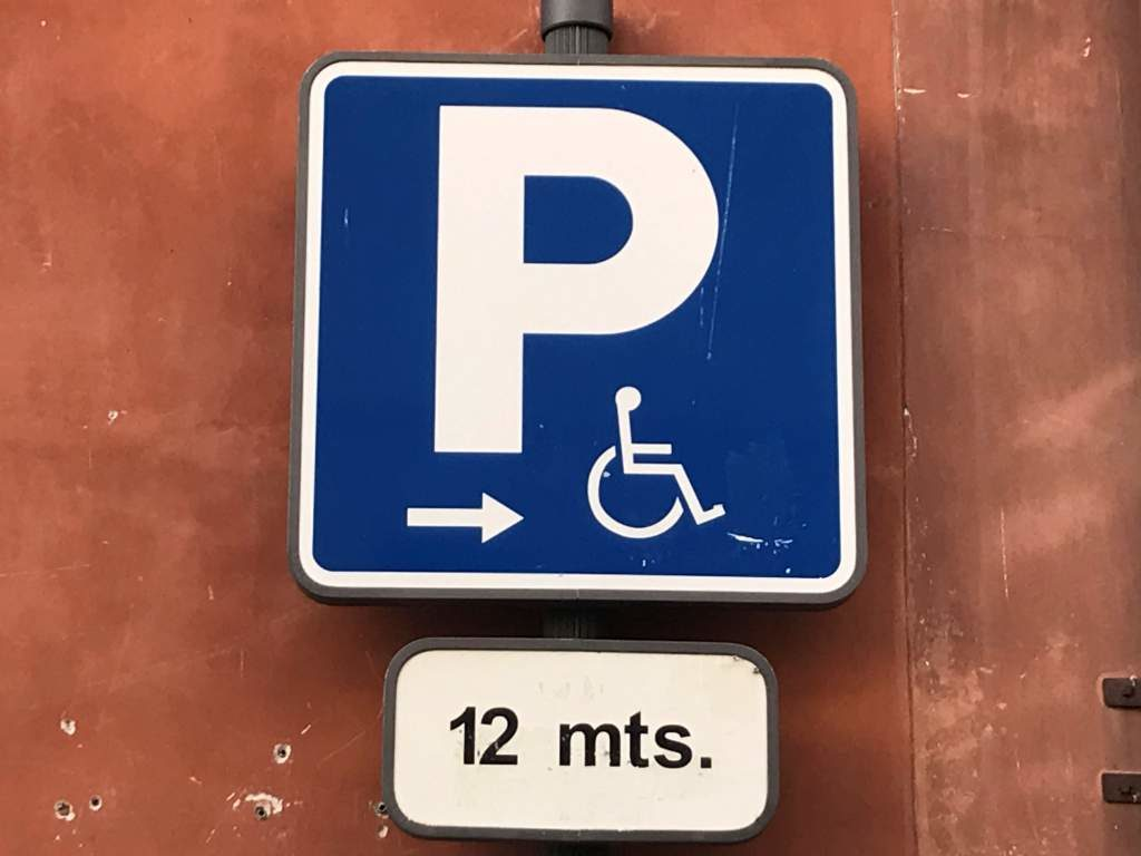 A parking sign showing wheelchair accessible parking in 12 meters.
