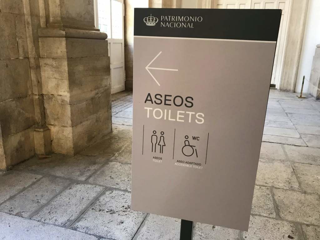 A sign pointing to a wheelchair accessible restroom in Aranjuez.