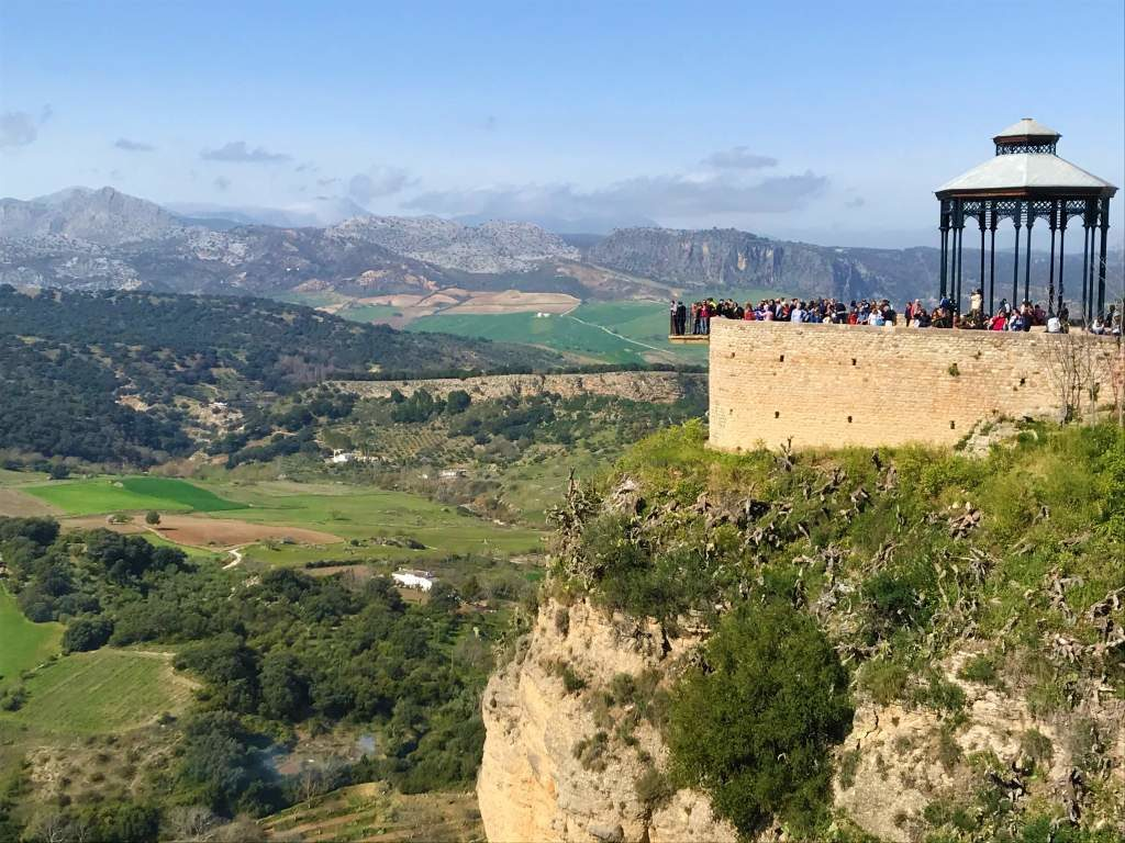 When taking a day trip from Seville to Ronda, stopping at the Balcón del Coño to hang over the ledge is a great option.