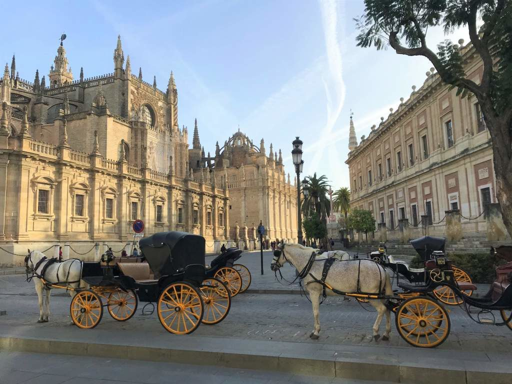 The Seville Cathedral with horse and buggies in the foreground.