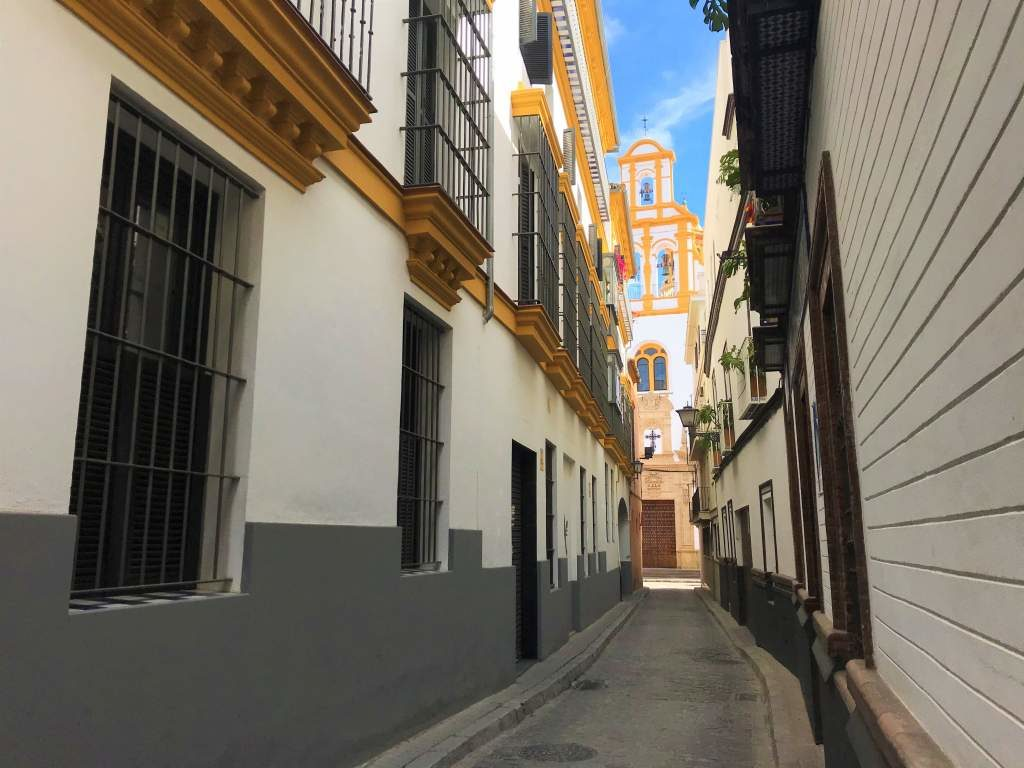 A narrow street in Seville that isn't wheelchair accessible.