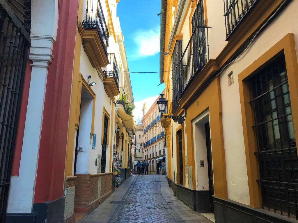 A narrow street in Santa Cruz, which makes for difficult wheelchair accessibility in Seville.