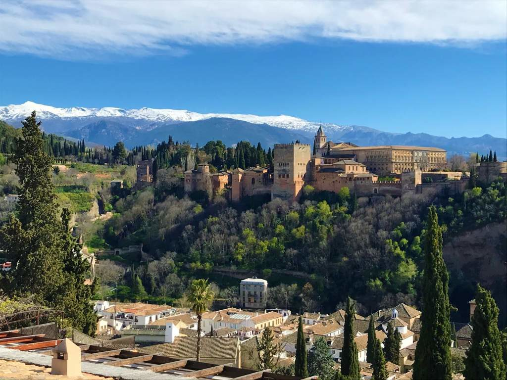 A view of the Alhambra with snow capped mountains in the backdrop.