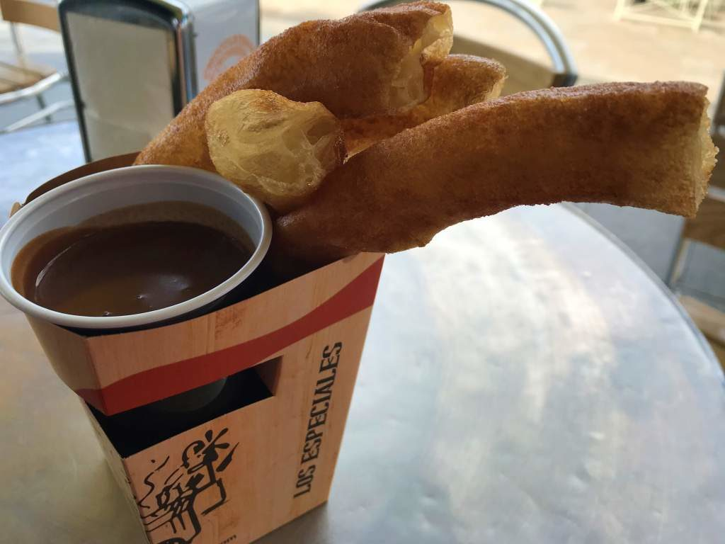 A to-go box of churros and hot chocolate.