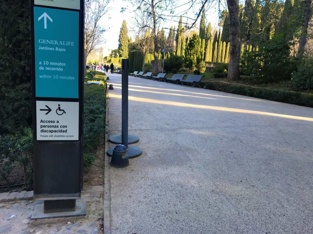 A paved path at the Alhambra and a sign pointing to the wheelchair accessible route.