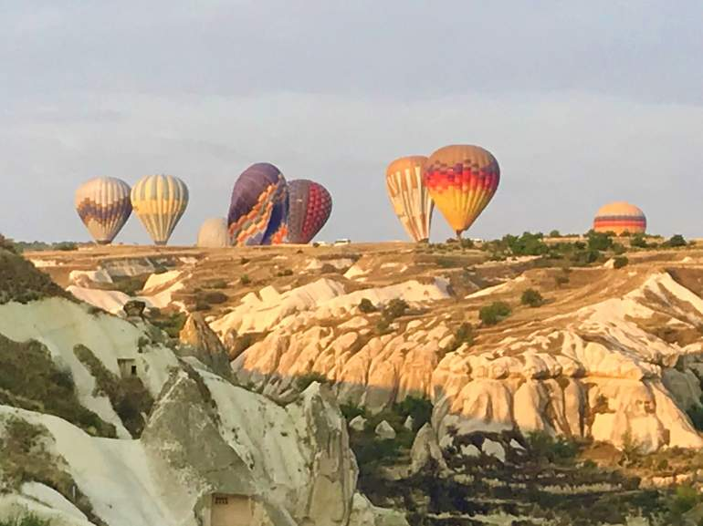 Balloons deflating in a rocky valley.