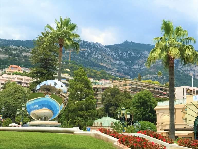 A park in Monaco with a mountain backdrop.
