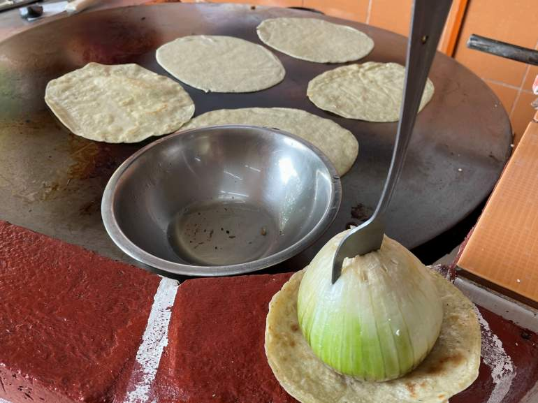 A grill with tortillas and an onion.