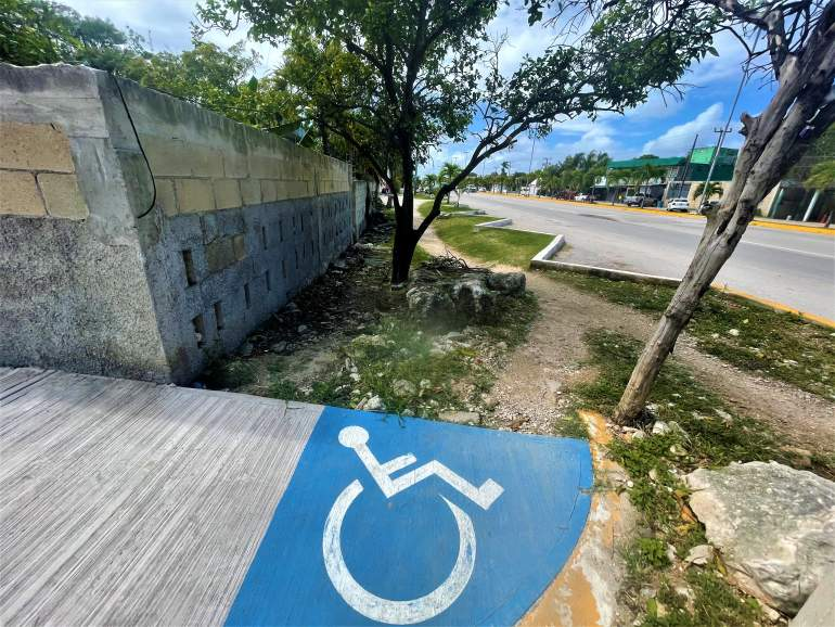 A wheelchair path in Tulum leading to dirt.