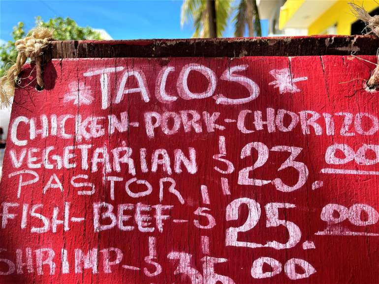 Sign showing taco prices. Budget is a big difference when comparing Tulum vs. Playa del Carmen.