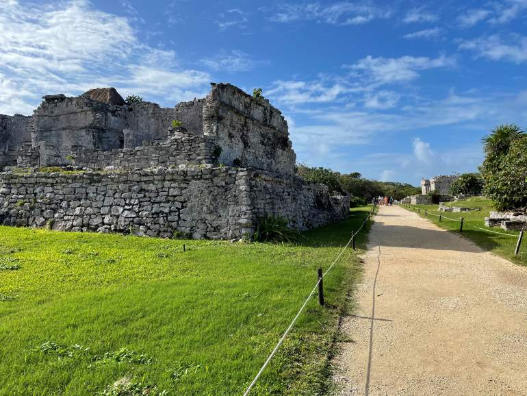 The Tulum ruins has a wide, dirt path and a low-lying rope fence.