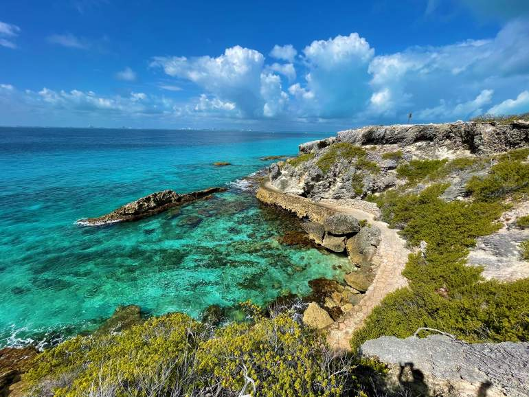A view of the blue water and rocky shore at Isla Mujeres.
