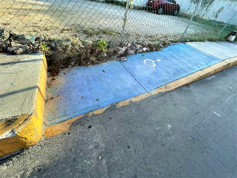 A wheelchair ramp blocked by a high cement step.