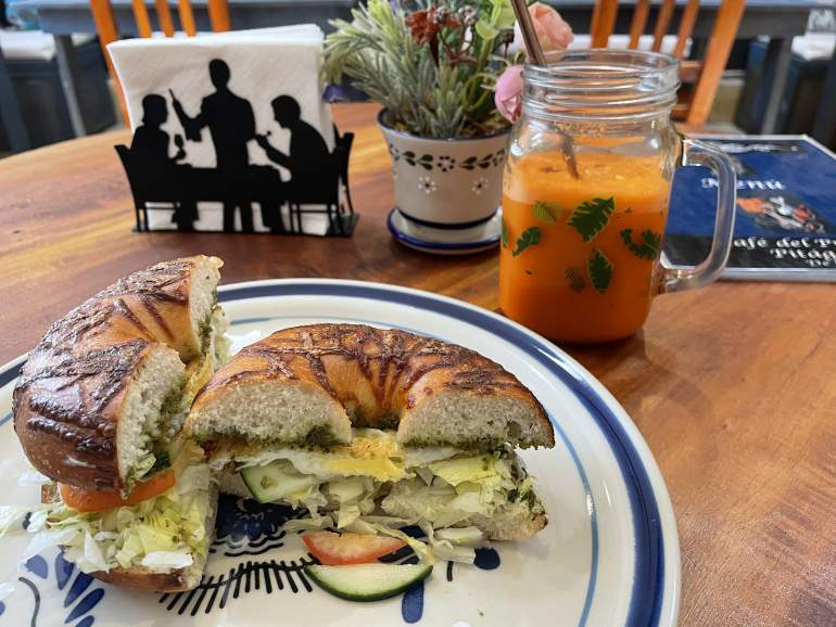 An egg sandwhich on a bagel with carrot juice.