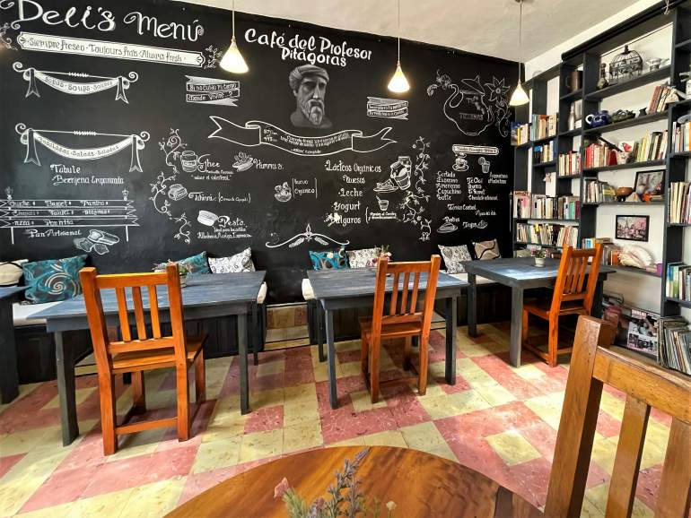 A bookshelf wall and tables inside Cafe del Pastor Pitagoras.