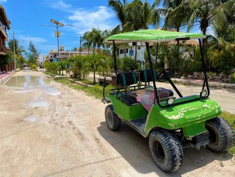 A golf cart near a muddy Holbox road.