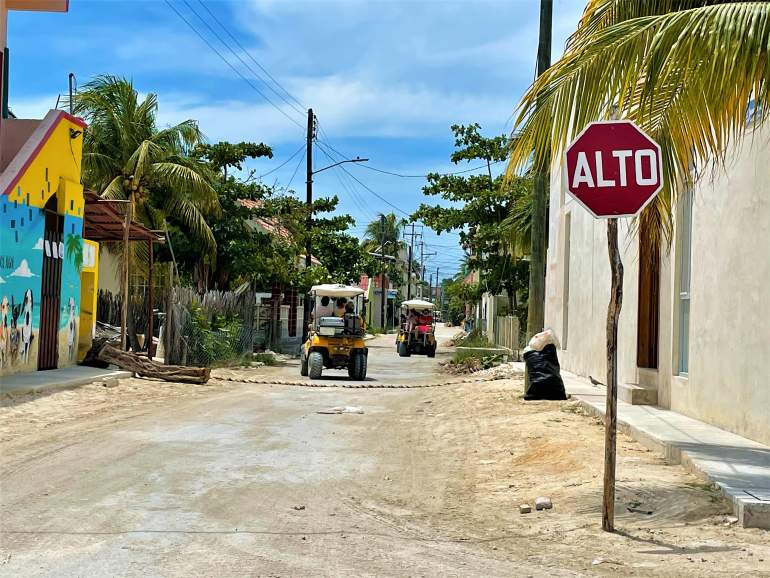 Golf carts on a dirt road in Holbox.